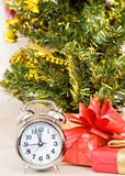 Soon new year!. Hours and a gift stand under a fir-tree royalty free stock photo
