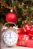 Soon new year!. Hours and a gift stand under a fir-tree stock photography
