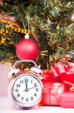 Soon new year!. Hours and a gift stand under a fir-tree stock photo