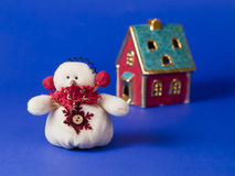 Soon the New Year. Toy snowman and house on a blue background stock photo
