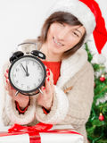 Soon new year!. Happy woman shows the clock on the background of the Christmas tree royalty free stock photos