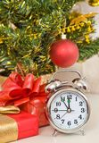 Soon new year!. Hours and a gift stand under a fir-tree stock image