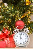 Soon new year!. Hours and a gift stand under a fir-tree royalty free stock photography