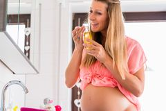 Soon-to-be mom scenting at bodycare oil. Pregnant woman reeking at skincare oil royalty free stock image