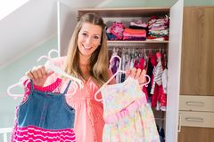 Pregnant woman in front of wardrobe in childs room. Soon-to-be mom shows girls clothes with anticipation in baby room stock photos