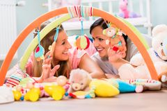 Women furnishing baby room preparing play bar for sucklings. Soon-to-be moms testing baby toys for neonates stock images