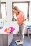 Heavily pregnant woman on scale in bathroom. Soon-to-be mother controlling her weight increase at person scale in bath stock images