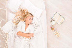 Soon to wake up for attractive blonde girl. Soon to wake up for young attractive blonde woman sleeping in bed stock photography