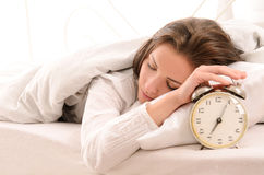 Soon to wake up for young woman. Soon to wake up for sleeping attractive young woman with alarm clock royalty free stock images