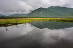 Soon it will rain. Azure lake with a reflection of the clouds of heaven at the foot of the mountains Stock Photo