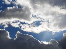 Soon it will start to rain, the blue sky through the clouds. Cloudy sky, gray clouds, soon it will start to rain, the blue sky through the clouds Royalty Free Stock Images