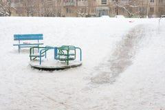 Soort de winter in een kleine die speelplaats van kinderen met ijsdia's wordt gevuld Royalty-vrije Stock Afbeelding