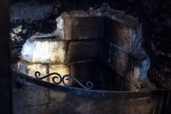 An old, rustic fireplace with dirty bricks and wrought iron fire screen. Soot, stains and burnt bricks gives this traditional fireplace a creepy, gothic look stock image