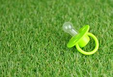 Soother on a green artificial grass lawn. Concept of caring for the hygiene and cleanliness of the baby. Soother on a green artificial grass lawn. Concept of royalty free stock photo