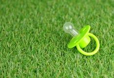 Soother op een groen kunstmatig grasgazon Concept het geven voor de hygiëne en de netheid van de baby royalty-vrije stock foto