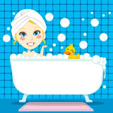 Soothing Bubble Bath. Pretty blond woman with white towel on her head taking a relaxing bubble bath in tub with rubber duck Royalty Free Stock Photo
