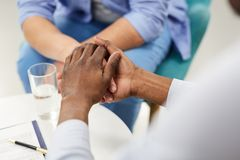 Soothing Hands. Close up of unrecognizable psychologist holding hands with patient in therapy session or support group, copy space stock photography