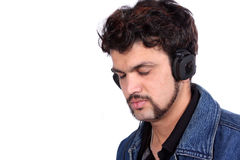 Soothing Music. A young Indian guy listening to peaceful soothing music on his headphones, on white studio background Stock Photo
