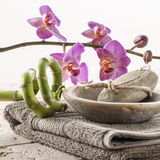 Soothing rejuvenation at home spa. Spa and spirituality concept - manicure polishing set with beige towel, bamboo and orchid flowers on mineral background for Stock Images