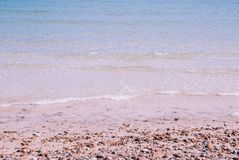 Soothing sea and rock beach, has some little wave. In sunny day royalty free stock photo