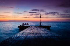Soothing Serene Haven. Soothing sunset on the serene haven by the seaside with dockage made of stone where people go swimming and fishing royalty free stock image