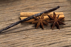 Soothing Spices. Cinnamon sticks, star anise and vanilla bean on a rustic wooden board Royalty Free Stock Photos