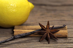 Soothing Spices with lemon. Cinnamon sticks, star anise and vanilla pod and a lemon in the background on a rustic wooden board Stock Photos