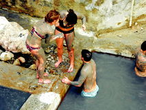 Soothing a Sunburn. After applying mineral-rich volcanic mud to the body, tourists immerse themselves in a bathing pool for a long therapeutic soak to remove stock images