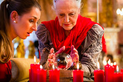 Soothsayer with crystal ball and client. Female Fortuneteller or esoteric Oracle, sees in the future by looking into their crystal ball answering questions from Stock Photography
