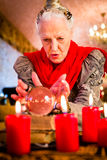 Soothsayer during esoteric session with Crystal ball. Female Fortuneteller or esoteric Oracle, sees in the future by looking into their crystal ball during a Stock Photography