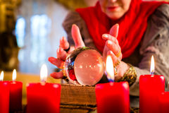 Soothsayer during esoteric session with Crystal ball. Female Fortuneteller or esoteric Oracle, sees in the future by looking into their crystal ball during a Stock Image