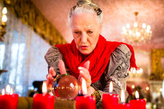 Soothsayer during esoteric session with Crystal ball. Female Fortuneteller or esoteric Oracle, sees in the future by looking into their crystal ball during a Royalty Free Stock Image