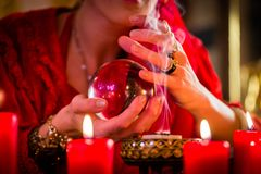 Soothsayer in Seance with Crystal ball and smoke. Fortuneteller or esoteric Oracle, sees in the future by looking into their crystal ball, incense burning and Royalty Free Stock Photography