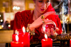 Soothsayer in Seance with Crystal ball and smoke. Fortuneteller or esoteric Oracle, sees in the future by looking into their crystal ball, incense burning and Stock Photography