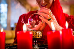 Soothsayer in Seance with Crystal ball and smoke. Fortuneteller or esoteric Oracle, sees in the future by looking into their crystal ball, incense burning and Royalty Free Stock Images