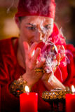Soothsayer in Seance with Crystal ball and smoke. Fortuneteller or esoteric Oracle, sees in the future by looking into their crystal ball, incense burning and Stock Photo