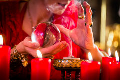 Soothsayer in Seance with Crystal ball and smoke. Fortuneteller or esoteric Oracle, sees in the future by looking into their crystal ball, incense burning and Stock Images
