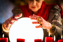 Soothsayer during a Seance or session with Crystal ball. Female Fortuneteller or esoteric Oracle, sees in the future by looking into their crystal ball during a Royalty Free Stock Photography