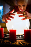 Soothsayer during a Seance or session with Crystal ball. Female Fortuneteller or esoteric Oracle, sees in the future by looking into their crystal ball during a Stock Image