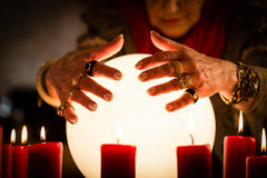Soothsayer during a Seance or session with Crystal ball. Female Fortuneteller or esoteric Oracle, sees in the future by looking into their crystal ball during a Stock Images