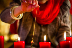 Soothsayer during a Seance or session with pendulum. Female Fortuneteller or esoteric Oracle, sees in the future by dowsing her pendulum during a Seance to Stock Photos