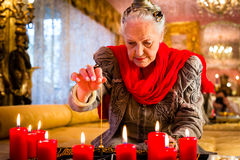 Soothsayer during a Seance or session with pendulum. Female Fortuneteller or esoteric Oracle, sees in the future by dowsing her pendulum during a Seance to Royalty Free Stock Photos
