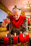 Soothsayer during a Seance or session with pendulum. Female Fortuneteller or esoteric Oracle, sees in the future by dowsing her pendulum during a Seance to Royalty Free Stock Images