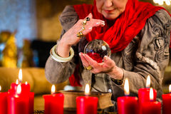 Soothsayer during session with crystal ball. Female Fortuneteller or esoteric Oracle, sees in the future by looking into their crystal ball Stock Image
