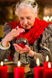 Soothsayer during session with crystal ball. Female Fortuneteller or esoteric Oracle, sees in the future by looking into their crystal ball Stock Photo