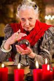Soothsayer during session with crystal ball. Female Fortuneteller or esoteric Oracle, sees in the future by looking into their crystal ball Royalty Free Stock Photography
