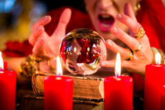 Soothsayer during session with Crystal ball. Female Fortuneteller or esoteric Oracle, sees in the future by looking into their crystal ball during a Seance to Royalty Free Stock Image