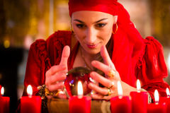Soothsayer during session with Crystal ball. Female Fortuneteller or esoteric Oracle, sees in the future by looking into their crystal ball during a Seance to Stock Photography