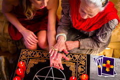 Soothsayer during a session doing palmistry. Female Fortuneteller or esoteric Oracle, sees in the future by hand reading during a Seance to interpret them and to Royalty Free Stock Photography