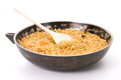 Sooty dripping pan of hot pilaf. Over white background Royalty Free Stock Photography